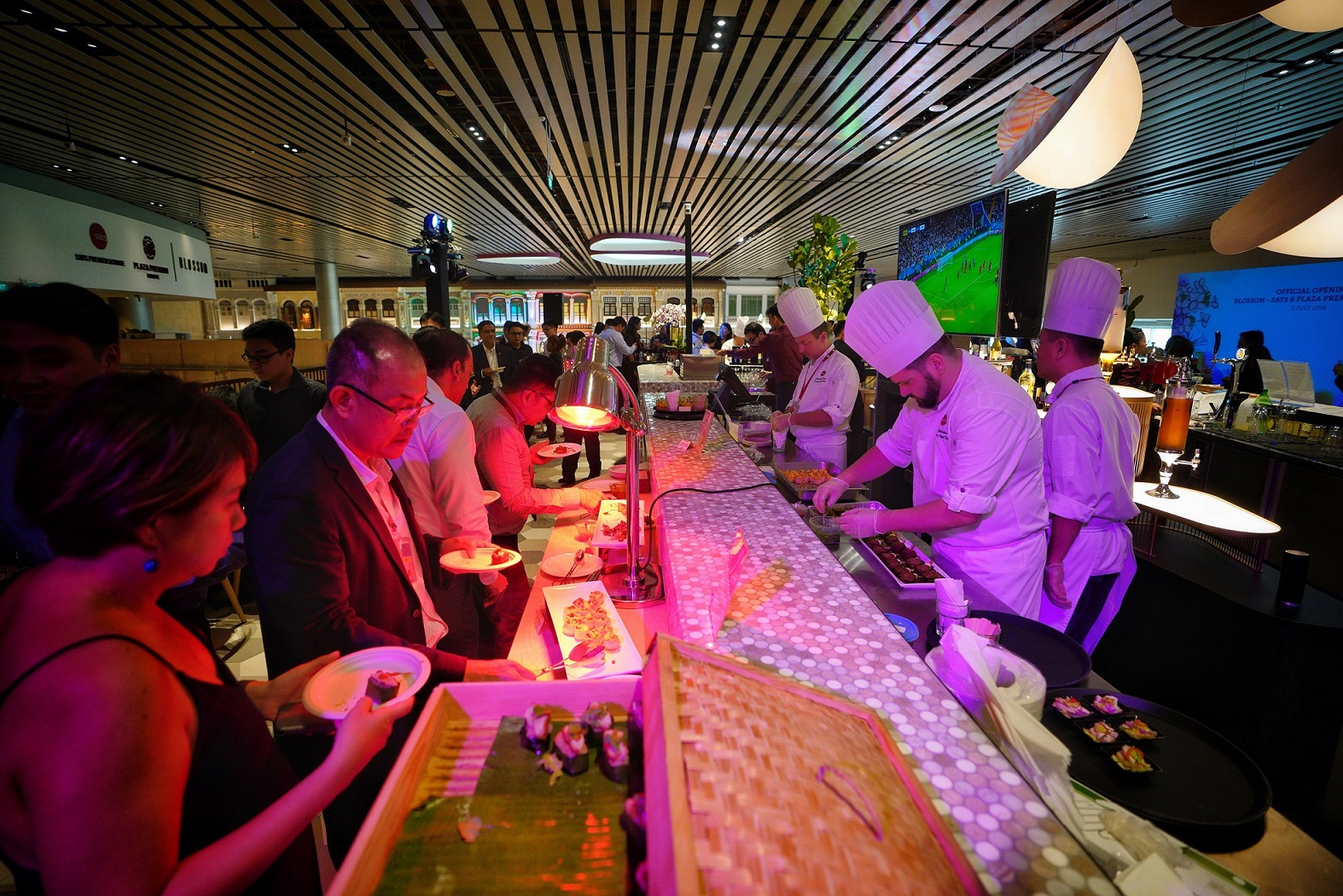 Chefs prepare food on the other side of the bar while guests feast are lined up at the buffet on the other