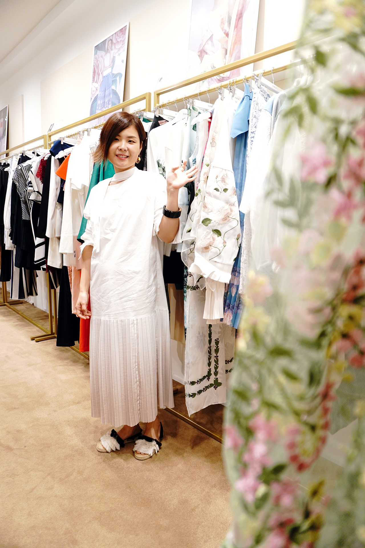 A woman wearing a white maxi dress is waving at the camera