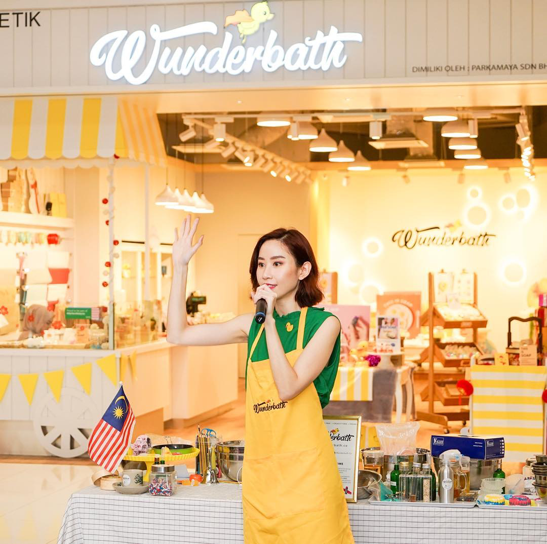 Woman wearing a yellow apron in front of a store.