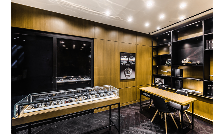 Interiors of a boutique with walnut wood walls and black carpet and a display case filled with timepieces