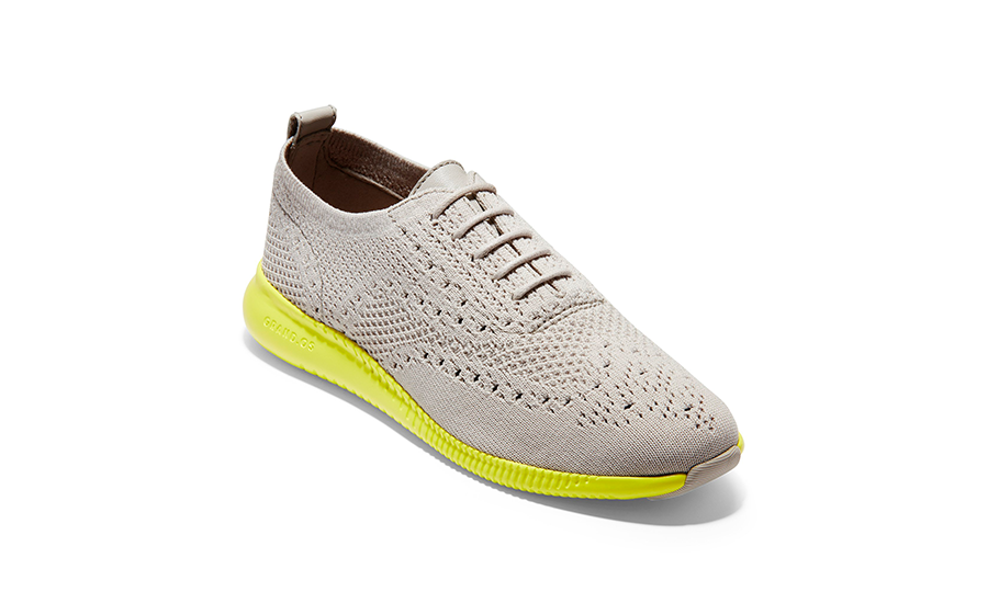 A grey knitted wingtip oxford shoe with neon green rubber outsole.