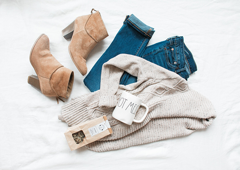 An outfit laid on bed consisting of a white sweater, suede boots, and jeans