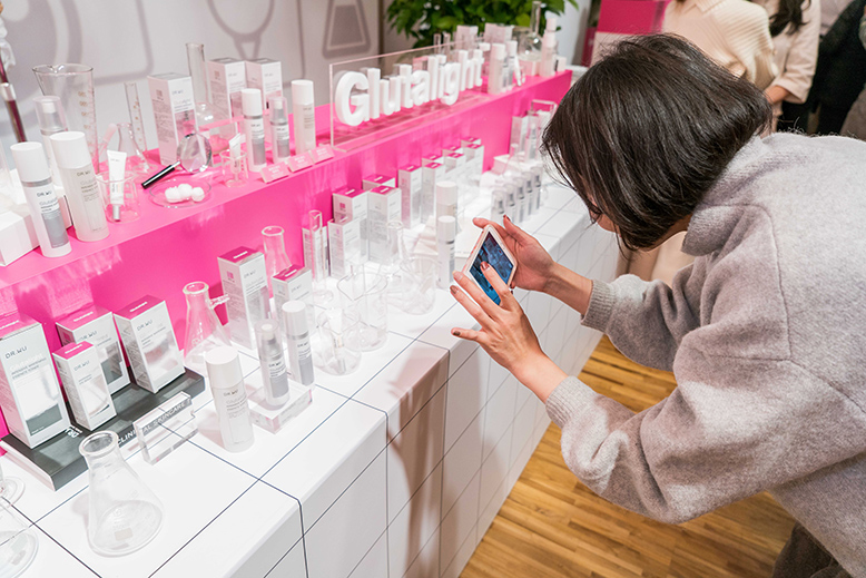 A woman with a bobbed hair takes a close-up photo of the Dr. Wu products lined up at a table with her phone.