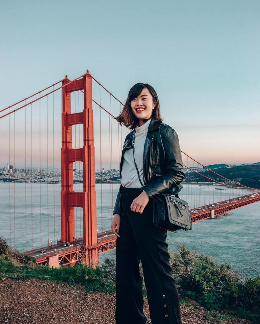 A woman wearing black wide leg trousers stands with the San Francisco bridge on her backgroud