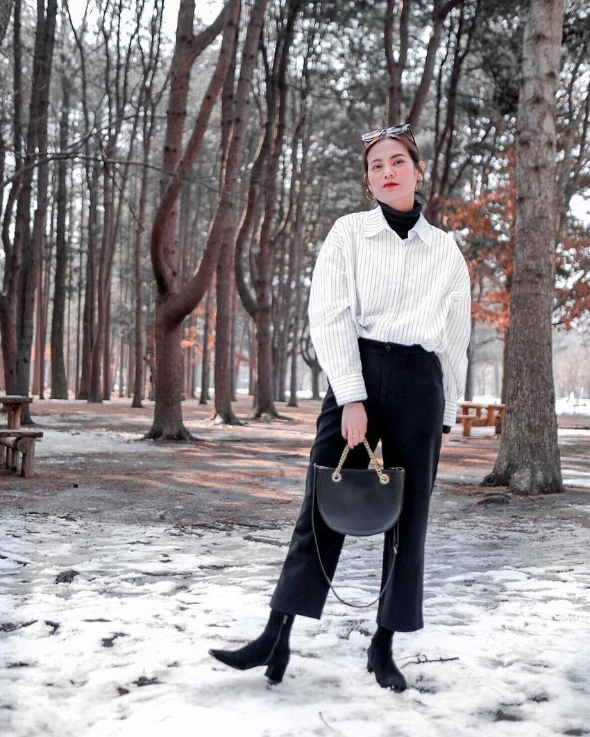 A woman wearing black cropped wide leg pants stands in the middle of the snow-covered forest