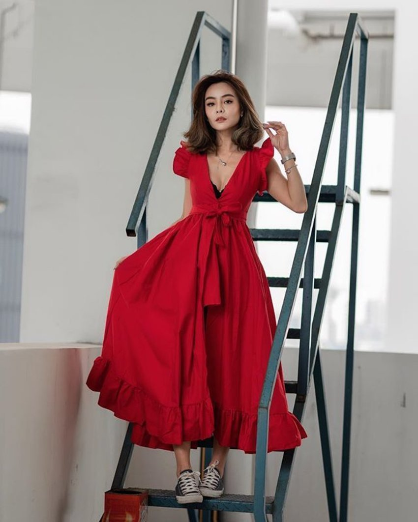 A woman wearing a red frilly wrap dress is standing on metallic stairs.