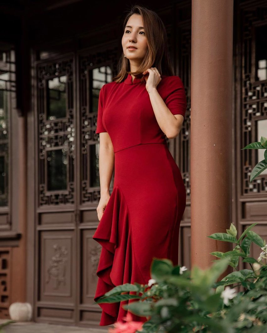 A woman wearing a modern red cheongsam is standing in front of a house with traditional Chinese architecture