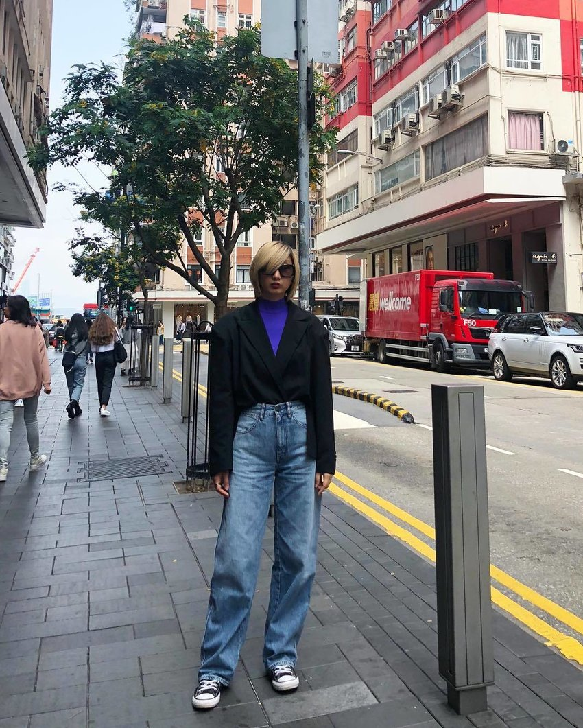 A woman wearing wide leg denim jeans stands in the middle of a busy street