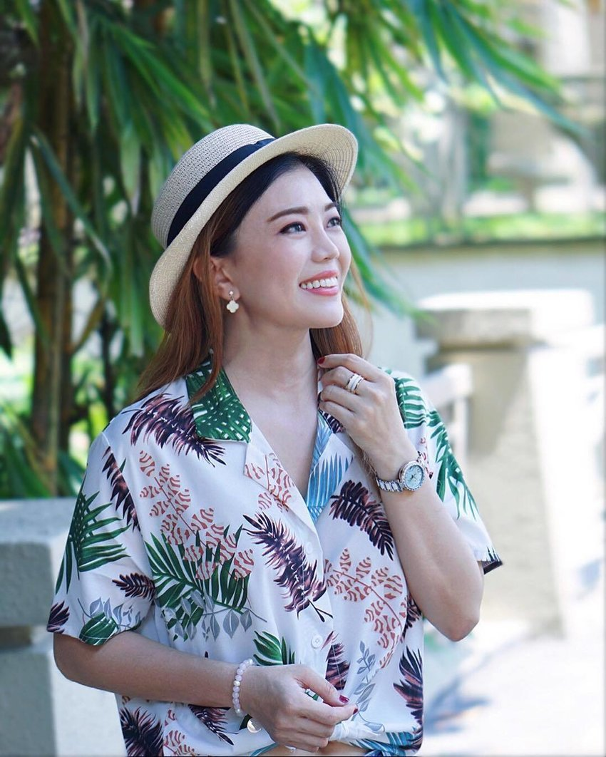 Woman wearing a boater hat and a tropical shirt