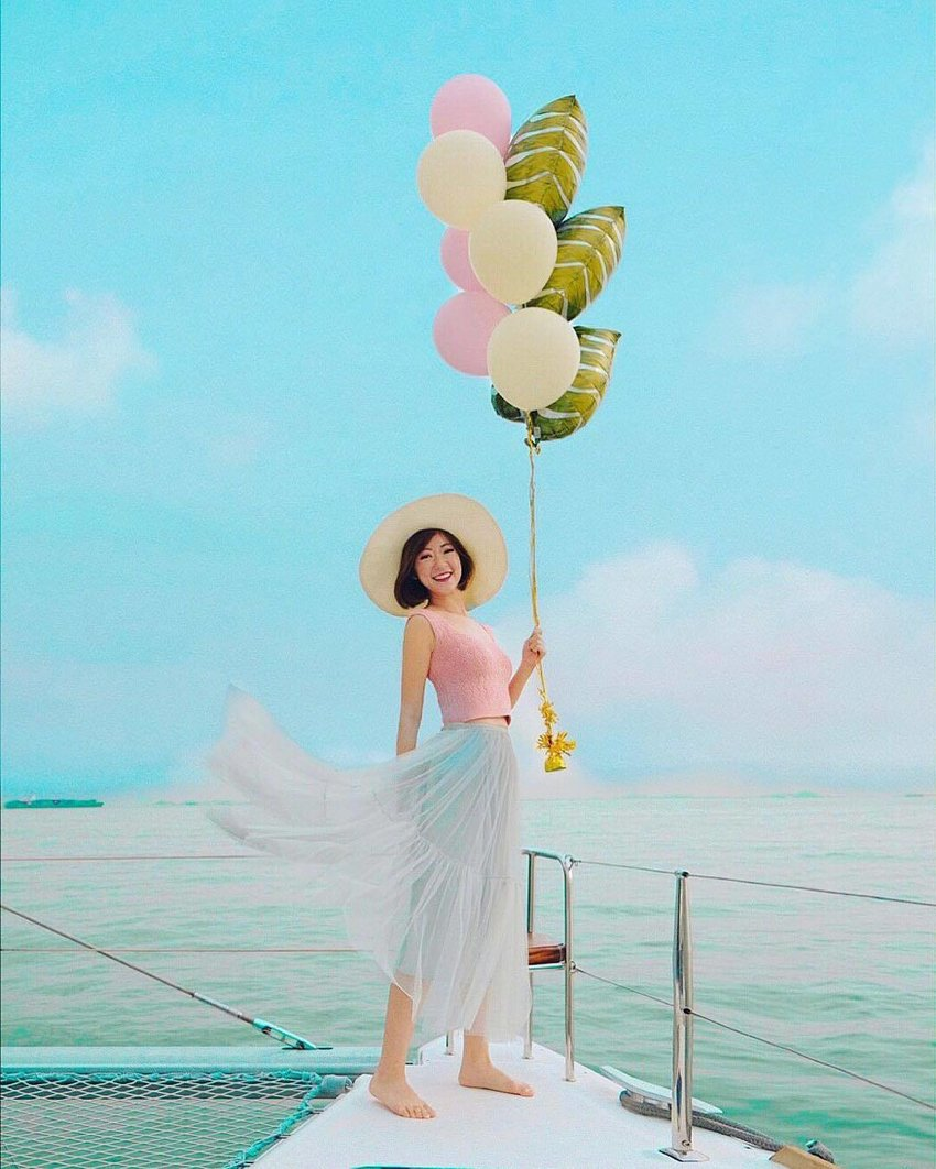 Woman wearing a straw hat and holding baloons on a yacht