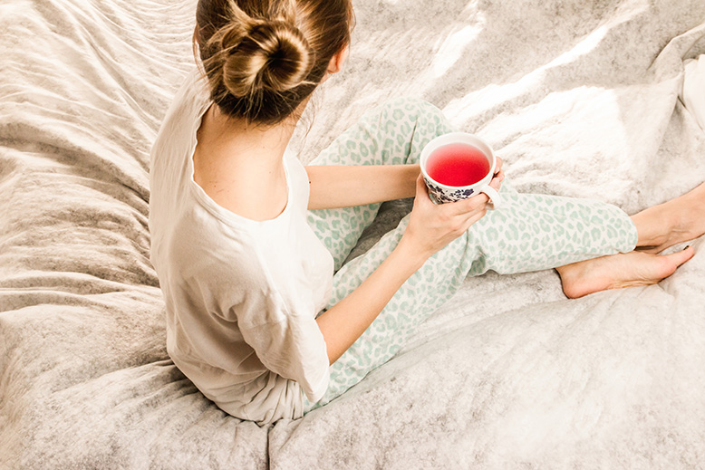 A girl is drinking tea on a bed