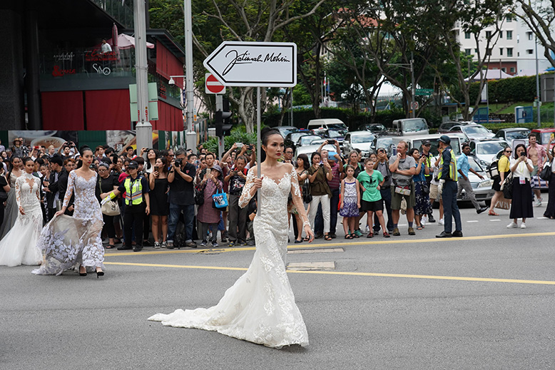 A model wearing a bridal gown holding up a picket that bears the name of designer Fatimah Mohsin