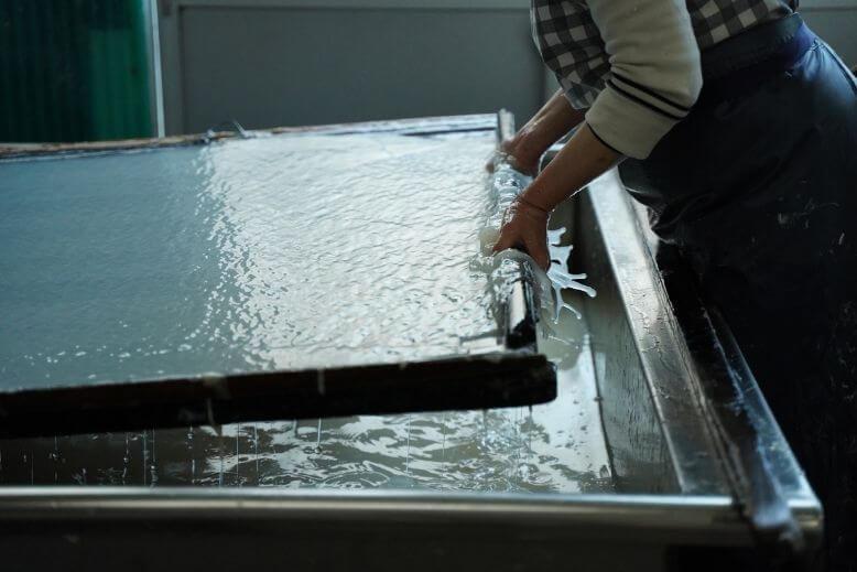 An artisan making washi notebook paper