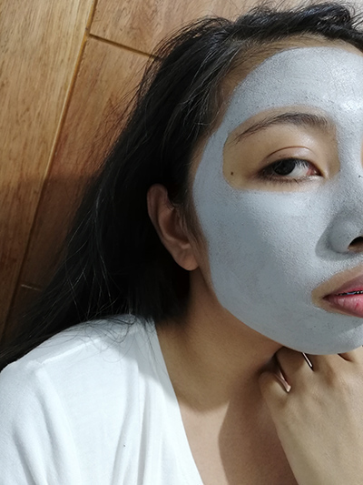 A photo of half a woman's face with the Innisfree Super Volcanic Pore Clay Mask spread on her it.