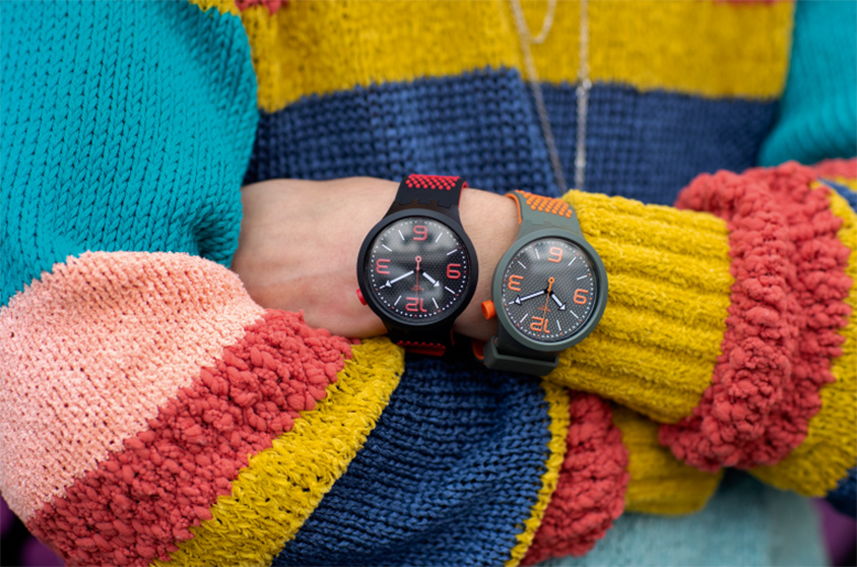 Person wearing a colourful sweater and two huge watches