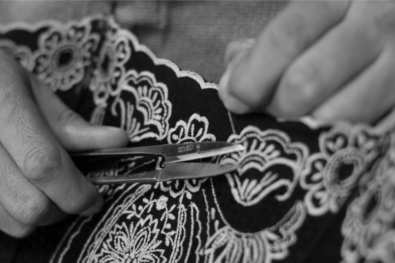 A black and white photo of someone cutting loose thread with scissors