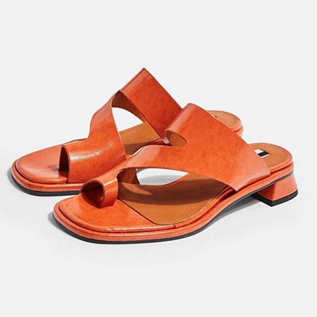 A pair of low-heeled orange faux leather sandals with toe loops.
