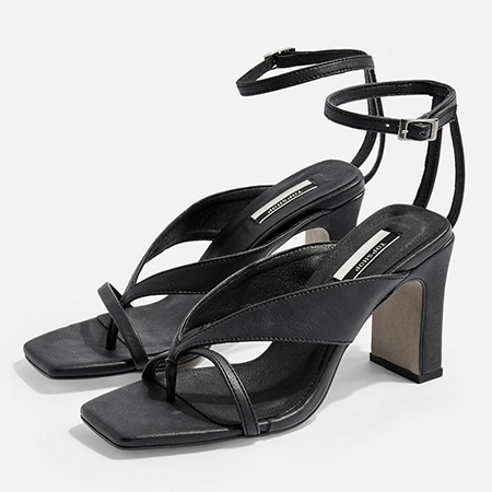 Black strappy sandals with high block heels made from vegan leather.