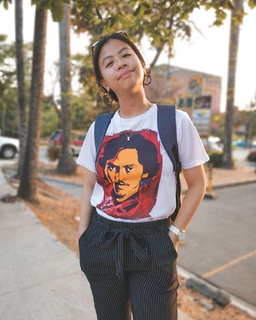 A girl wears a graphic t-shirt with a face of a moustached man printed on it.